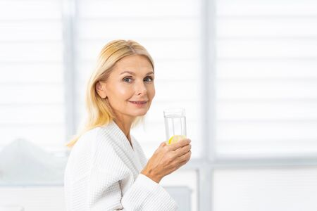 Portrait of a contented female patient with loose blonde hair standing in a dermatologists office