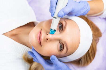 Top view of a pleased blonde woman enjoying a cosmetic procedure in a dermatologists office