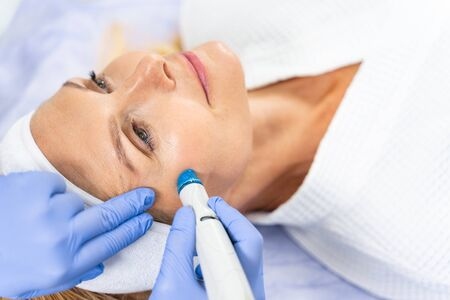 Close up portrait of a female patient getting a facial skin treatment in a beauty clinic