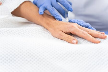 female patient undergoing a hand rejuvenation treatment in a dermatologists office