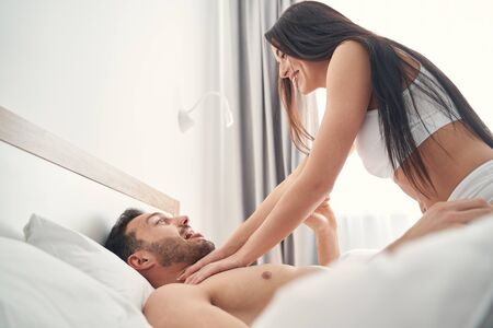 Joyful dark-haired Caucasian woman in underwear playing with her young husband in bed Banque d'images