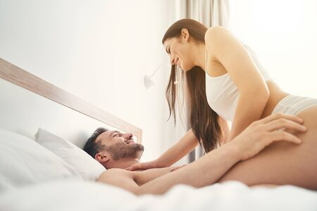 Smiling playful young lady in lingerie sitting on top of her happy husband in bed