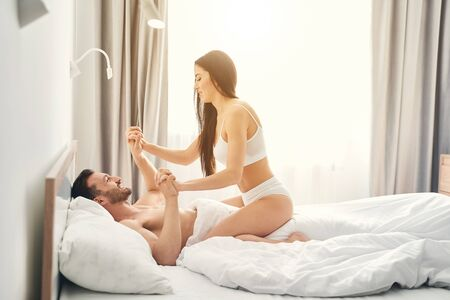 Side view of a slim woman in lingerie having fun with her husband