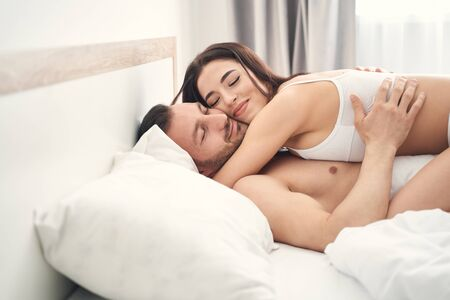 Cute young Caucasian man and his pleased wife lying in bed with their eyes closed