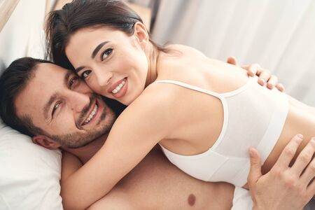 Close up portrait of a smiling contented young couple hugging each other in bed