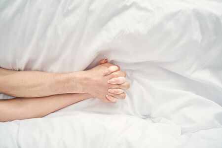 Top view of the male and female hands with intertwined fingers lying on the bed