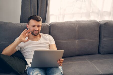 Handsome brunette man waving his hand while communicating online from home using his laptop