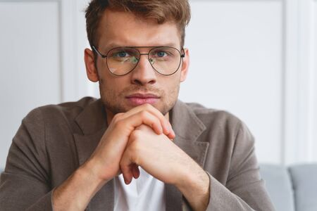 Close up of attractive gentleman in glasses propping up head with hands and looking at camera with serious expression