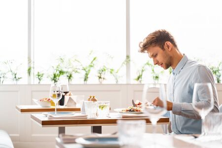 Good-looking man in shirt sitting at the table and eating delicious food in cafe