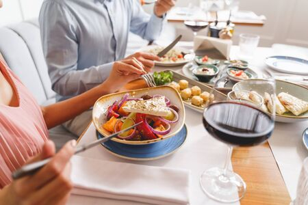 Close up of man and woman sitting at the table and eating delicious food in cafe