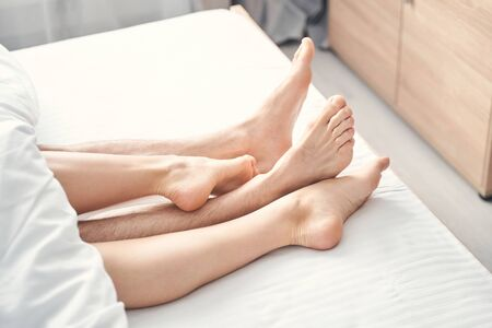 Close up of female and male legs sticking out from under the blanket in a bedroom