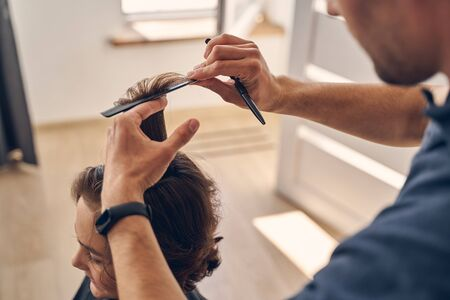 Small child sitting quietly while hairdresser cutting hair and using scisors and comb at home