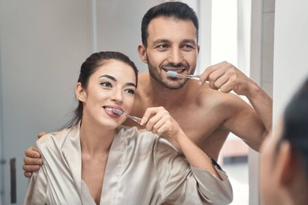 Happy young beautiful man and woman in love standing at the mirror in bathroom and cleaning their teeth