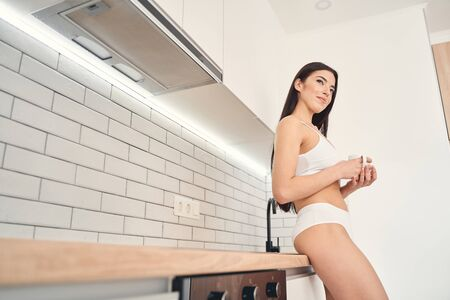Young beautiful dark-haired woman in fashionable underwear standing and holding cup of hot drink in hands