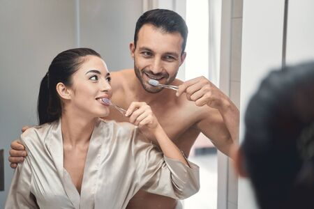 Nice-looking smiling husband and wife brushing teeth at morning and standing close to one another near the mirror