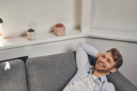 High-spirited cute young Caucasian man lying on his back on the edge of the sofa