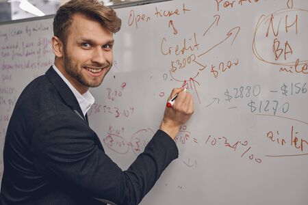 Close up portrait of a high-spirited young businessman with a marker pen posing for the camera
