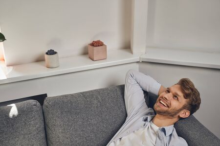 Merry attractive bearded young male entrepreneur lying on the couch in his modern office
