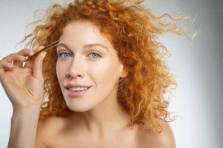 Portrait of cheerful curly female plucking eyebrows with cosmetic tongs isolated on grey background