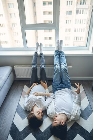Lovely pregnant lady and her husband wearing similar clothes and lying on the carpet with their feet on a window sill