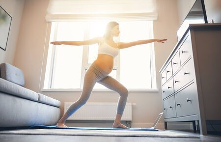 Pretty pregnant lady standing on the yoga mat in the warrior pose next to the window on sunny day