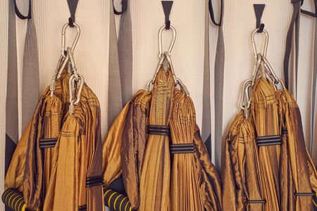 Close up of hanging yoga stripes for aerial yoga exercise or antigravity yoga hanging on hook on the wall 免版税图像