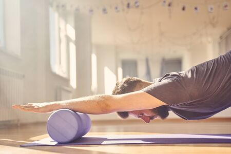 Serene bearded man placing hands on yoga roller block and meditating in yoga studio
