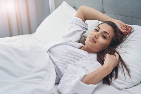 Attractive lady looking at camera and smiling while resting in bedroom