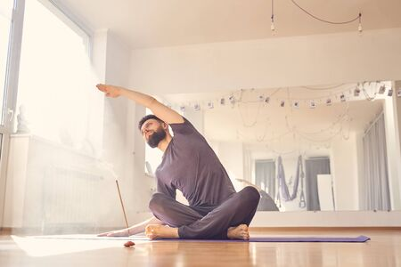 Handsome male practicing yoga while sitting on the floor with incense stick Stock fotó