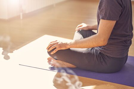 Close up of male yoga instructor sitting on the floor and meditating Stock fotó