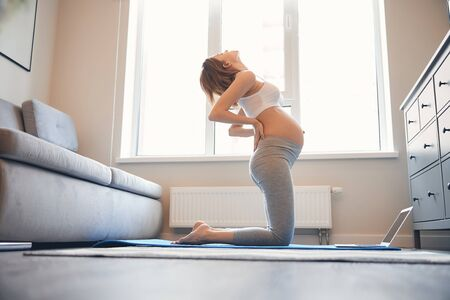Young pregnant woman standing on her knees on the yoga mat at home in front of a laptop and bending backwards