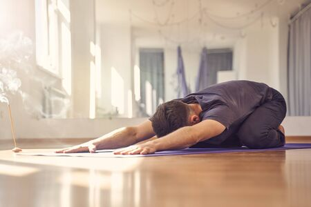 Athletic male sitting on yoga mat and extending arms in front of him while practicing yoga