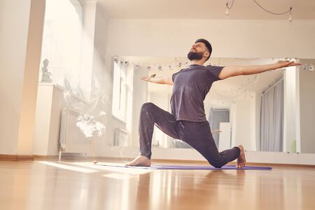 Good-looking male practicing yoga in yoga studio with incense stick on the floor