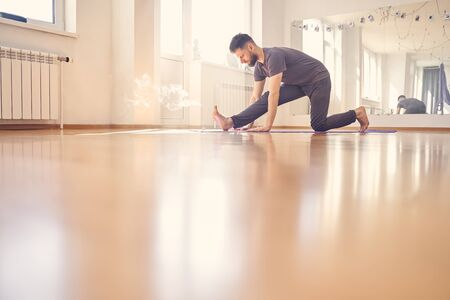 Handsome young man in shirt and sport pants practicing yoga in studio with incense stick on the floor
