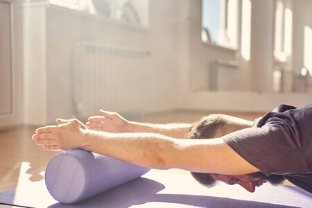 Close up of bearded male placing hands on yoga foam roller and meditating in yoga studio