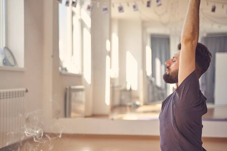Serene young man closing eyes and raising hands while meditating during yoga practice