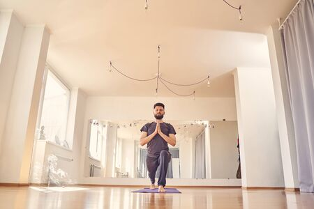 Handsome bearded man in shirt and sport pants doing yoga exercise and meditating