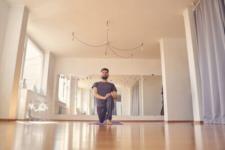 Serene bearded male doing exercise in yoga studio with incense stick on the floor