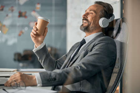 Relaxed smiling man in headphones enjoying good music on laptop with eye closed