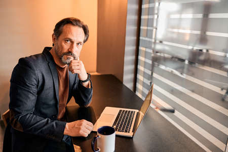 Confident serious bearded businessman working on the laptop while sitting at the black table