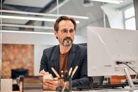 Confident businessman in eyeglasses and brown shirt sitting at the table and looking at computer screen with serious facial expression Foto de archivo