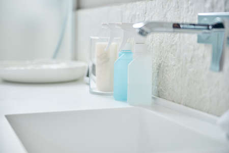 Close up photo of two spray bottles standing on the sink next to the basin in the bathroom