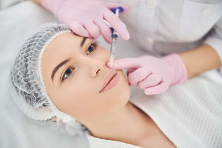 Young woman peacefully resting with open eyes while experienced cosmetologist applying a filler into her upper lip
