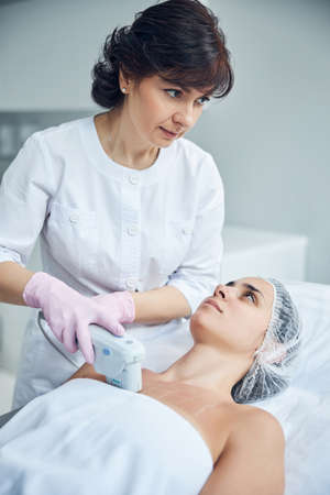 Focused cosmetologist using effective high technology apparatus while performing anti aging decolletage therapy