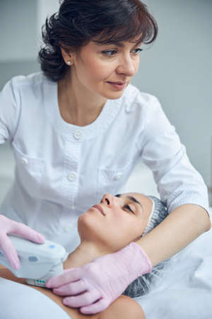 Mature beauty expert using modern apparatus while looking away and performing non surgical decolletage skin tightening Banque d'images