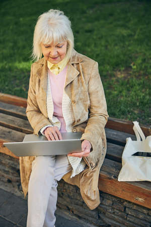 Female pensioner typing on laptop while sitting on the bench