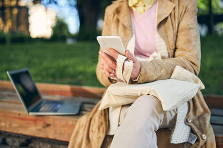 Cropped head of mature woman with grey laptop sitting on bench while texting in her mobile
