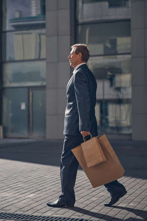 Good-looking gentleman holding shopping bags and strolling down the city