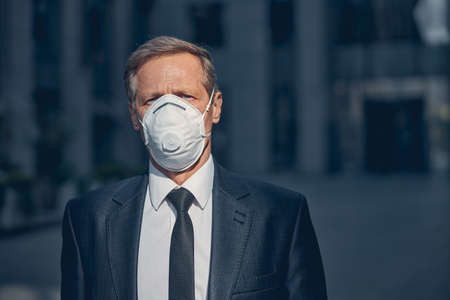Elegant gentleman in medical face mask looking at camera while spending time outdoors Archivio Fotografico