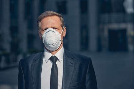 Elegant gentleman in medical face mask looking at camera while spending time outdoors Reklamní fotografie